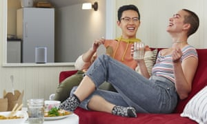 Two people sit in a room with a smart speaker