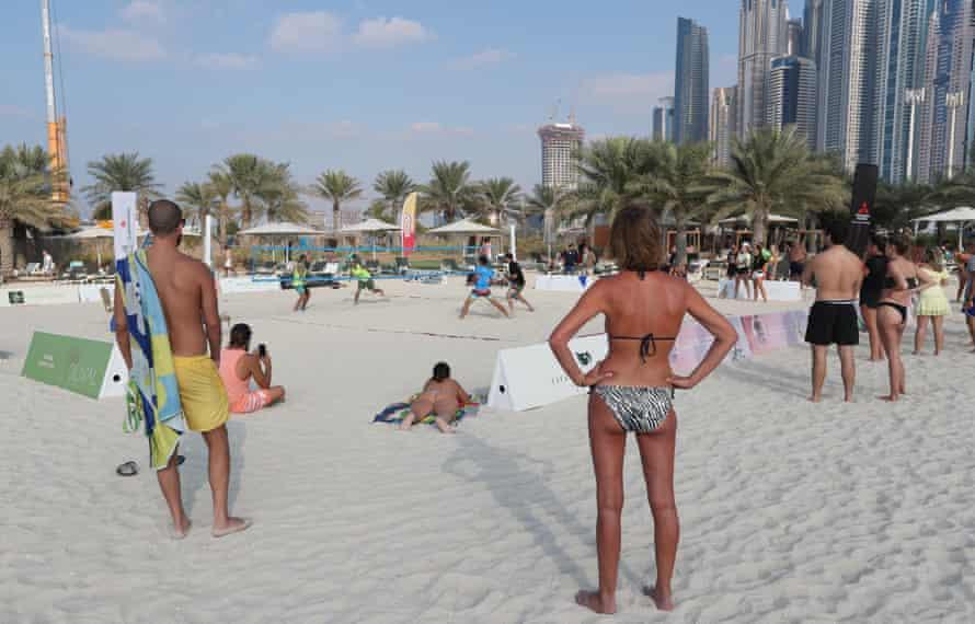 People enjoying the sunshine while watching beach tennis in Dubai
