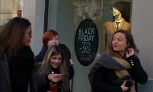 People walk past a shopfront advertising 'Black Friday' discounts in Madrid, Spain.