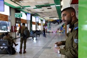 An Israeli soldier smokes as he waits with others to board buses at a terminal at the Central Bus Station