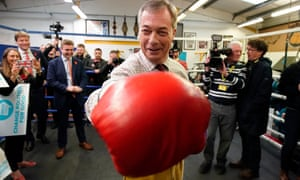 Nigel Farage wearing red boxing gloves makes a punch at the camera