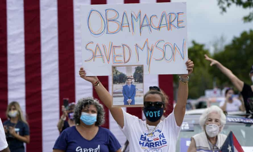 Adelys Ferro holds a sign in support of Obamacare on 24 October 2020 in North Miami, Florida.