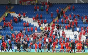 Players applaud the fans in the stands at the end of the match.