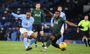 Manchester City's Raheem Sterling shoots at goal as Tottenham Hotspur's Japhet Tanganga attempts to block.
