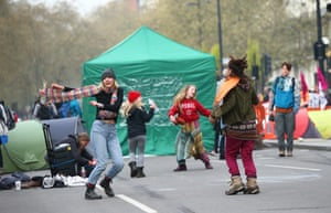 Extinction Rebellion protesters dance in the traffic-free road