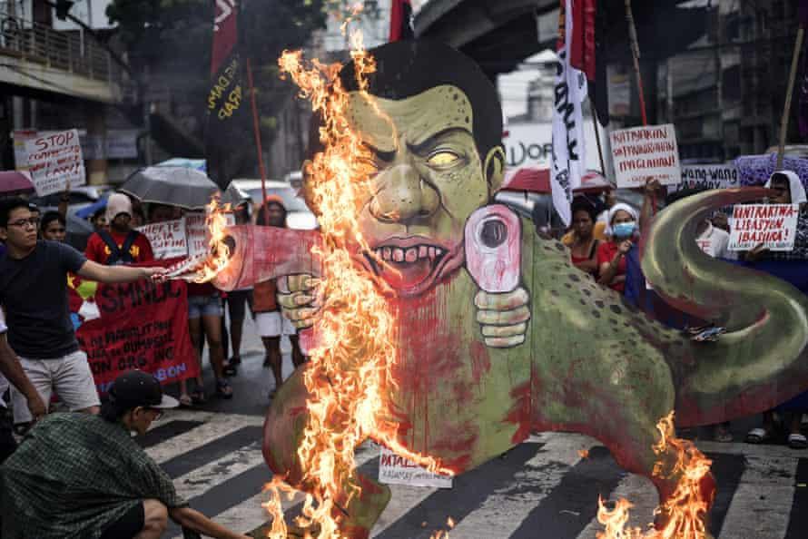 Activists burn a caricature of Philippine president Rodrigo Duterte as a gun-toting dinosaur.