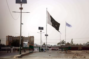 A flag of the Afghan Taliban (in white) is raised at the  Pakistani-Afghan border.