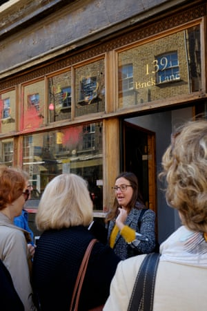 A tour guide speaks to tourists outside Cereal Killer Cafe, which was daubed with paint and cornflakes as part of a protest against gentrification in the area
