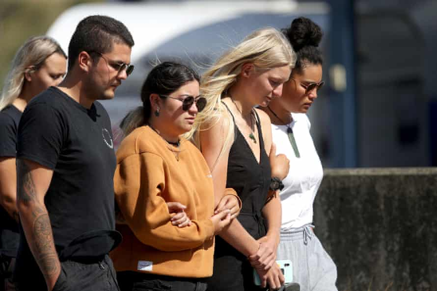 People are seen grieving and comforting each other outside the Te Manuka Tutahi Marae