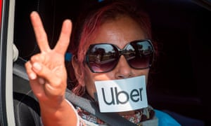 A protester gestures as Uber and Lyft drivers drive through Beverly Hills on Wednesday to demonstrate outside the $72m home of the Uber co-founder Garrett Camp.