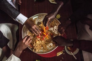 Men share a dish of pilau rice for lunch during Eid Mubarak celebrations