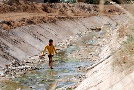 An Iraqi boy walks through a dried up irrigation dyke in the village of Sayyed Dakhil, 180 miles south of Baghdad.
