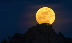 A full moon rises with the silhouette of an astronomer and telescope in front.