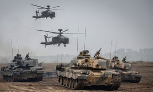 Apache helicopters hover above a column of Army vehicles on exercise on Salisbury Plain.