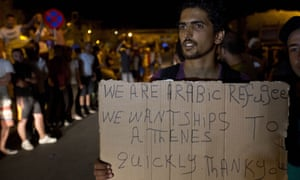 A Syrian migrant holds a banner on the Greek Island of Lesbos after crossing the Aegean from Turkey. Greece this year has been overwhelmed by record numbers of migrants arriving on its eastern Aegean islands. (AP Photo/Visar Kryeziu)