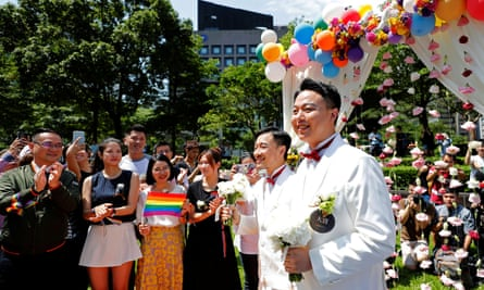 Newlyweds walk on a giant rainbow flag at a pro same-sex marriage party after registering their marriage in Taipei.