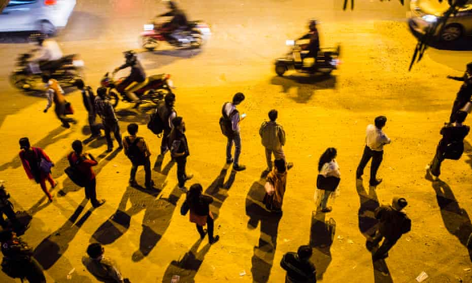 Commuters wait for their buses during the evening rush hour outside Nehru Place in Delhi.