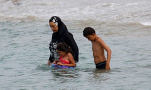 A Muslim woman enters the sea in a burkini.