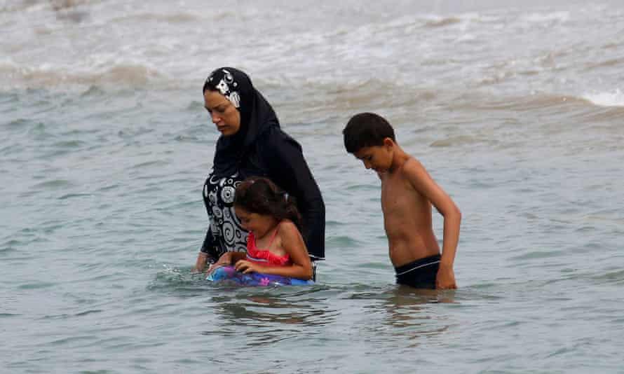 A Muslim woman enters the sea in a burkini.