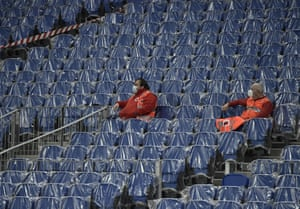 Two Red Cross workers sit in seats covered with plastic in an almost empty stadium during the Europa League Group F soccer match between Real Sociedad and AZ Alkmaar at the Anoeta stadium in San Sebastian, Spain.