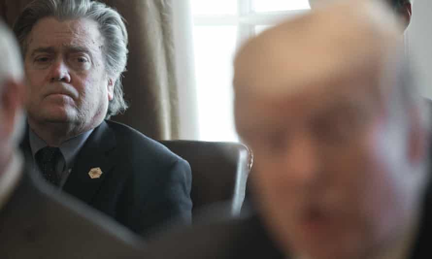 Steve Bannon listens as Donald Trump speaks to the press in the Cabinet Room of the White House.