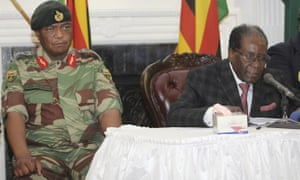 Zimbabwean President Robert Mugabe flanked by the Army Chief Chiwenga delivers his speech during a live broadcast at State House in Harare