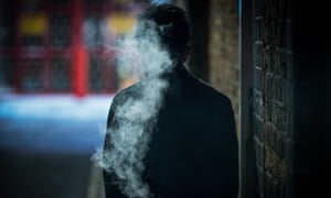 Man smoking in a dark alleyway.