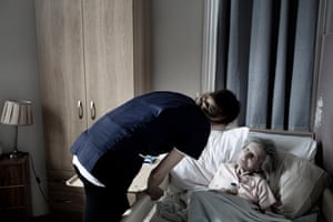 Nursing assistant Kasia Kapuscinska talks with 97-year-old Sybil Thompson, a resident at St Cecilia's Nursing Home in Scarborough, Yorkshire.