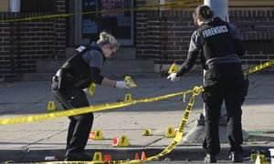 Police forensics officers at the scene of the shooting in Baltimore in which one person died and seven were wounded.