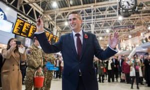 The new defence secretary, Gavin Williamson, conducts the Band of the Grenadier Guards at Waterloo station hours after his appointment.