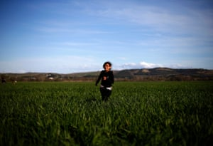 A girl runs through a field of grass close to the makeshift camp for migrants near the Greek-Macedonian border in Idomeni, Greece