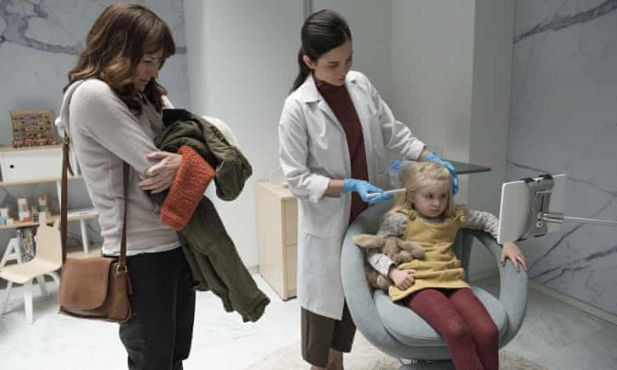 Amother (Rosemarie Dewitt) watches as a surveillance chip is inserted into her daughter (Aniya Hodge) in the Jodie Foster-directed Black Mirror episode Arkangel