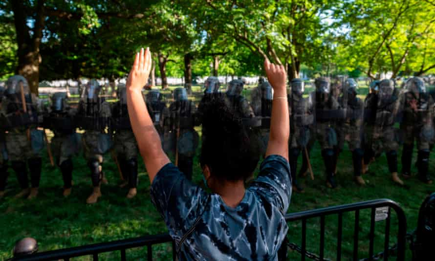A protester raises her hands near a line of National Guard soldiers, near the White House on Monday.
