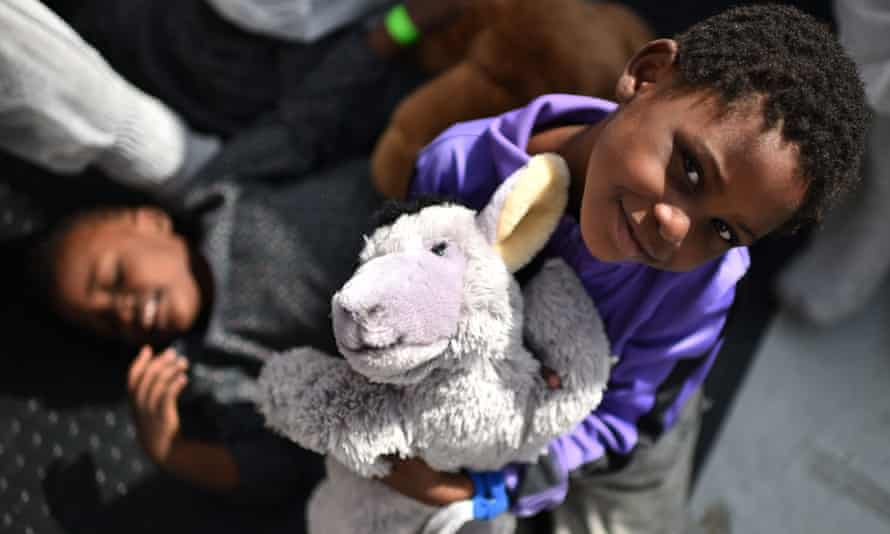 A refugee child smiles during a distribution of meals aboard a rescue ship.
