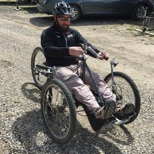 Jonathan sitting in an adaptive bike with two wheels at the front and one at the back