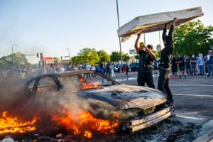 Protesters throw a mattress onto a burning car