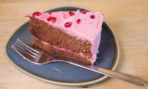 A slice of chocolate cake with bright pink icing and with pomegranate seeds on top