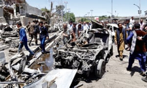 People survey the the scene of a suicide bomb attack in Kabul.