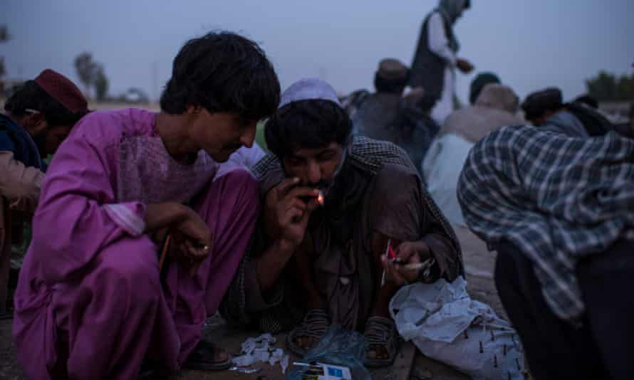 Opium addicts gather to smoke by a wall in a public park in Lashkar Gah, the capital of Helmand province, where half of Afghanistan's opium is produced.