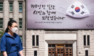 A woman wearing a face mask as a preventive measure walks under the campaign banner on the wall of Seoul city hall in South Korea.