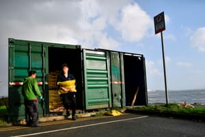 People take sandbags from a storage shed to protect their homes on the Dublin Bay coast