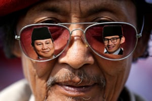 a mean wears glasses showing images of Prabowo and his running mate