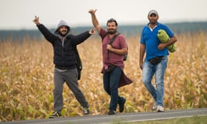 Migrants make their way along a road after crossing the border between Austria and Hungary near Heiligenkreuz.
