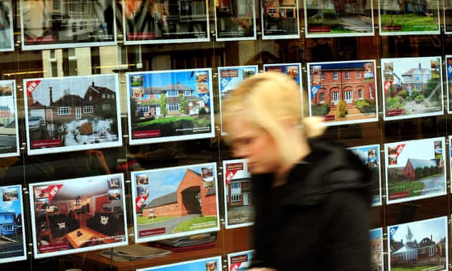 Awoman walking past a estate agent's window.