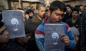 Kashmiri Shiite Muslims mourn as they hold portraits of Sheikh Nimr al-Nimr.