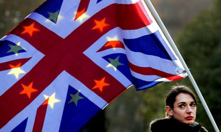 A protestor holds flags British and EU flags against the sunlight.