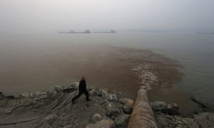 A man walks by a pipe discharging wastewater into the Yangtze River from a paper mill in Anqing, Anhui province.