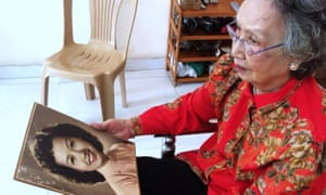 Trinh Thi Ngo photographed in 2015 at her Ho Chi Minh City home with a portrait of her younger self.