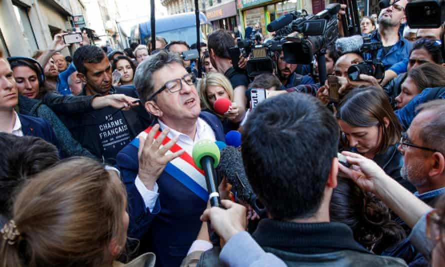 Jean-Luc Mélenchon on the street surrounded by reporters.