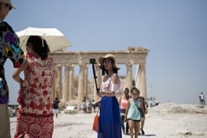A tourist takes a selfie in front of the Parthenon temple in Athens. All Greek archaeological sites will shut during the hottest hours of the day this week.